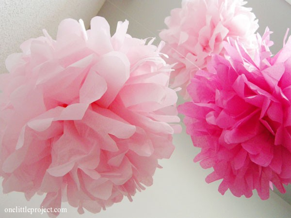 pink tissue paper pom poms suspended from ceiling