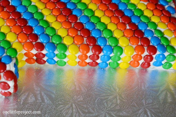 Rainbow M&M's first birthday cake | onelittleproject.com