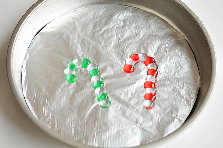 These melted bead candy canes are SO EASY to make with pony beads and they're the cutest homemade Christmas ornaments ever! They look beautiful on the tree, or you can use them as sun catchers in the window!