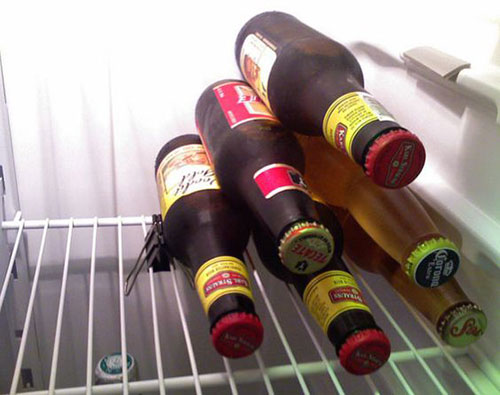 25 Hacks to Organize your Fridge - Use binder clips to help keep bottles neatly stacked on their sides