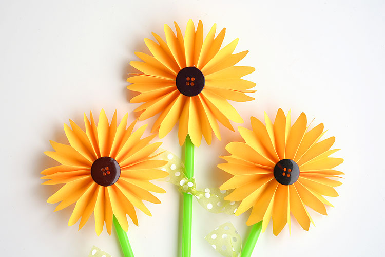 These folded paper sunflowers are SO PRETTY! And they're so easy to make! This is such a great craft project for summer or would even make a great fall craft! I love the button in the middle!