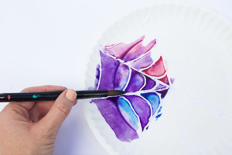 This watercolor kids art project webs use hot glue and paint to create beautiful spider webs!