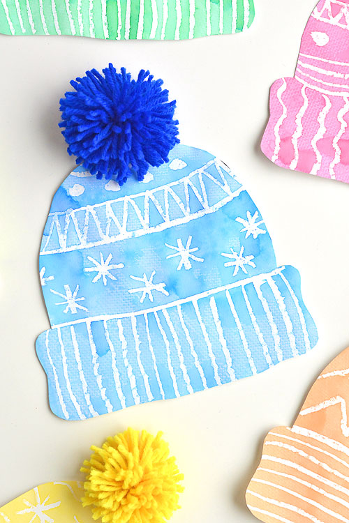 This winter hat art project for kids is such a fun winter craft idea! Use the free printable winter hat template to have a fun day of crafting at home or in the classroom! This process art idea lets you experiment with creating texture in watercolor and shows the magic of painting over crayon with watercolour paint! There's even instructions for making a DIY yarn pom pom!
