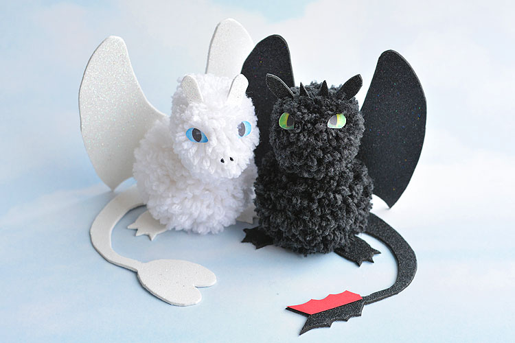 These pom pom dragons, inspired by How to Train Your Dragon: The Hidden World (in theaters February 22) are so fun! You can easily make Toothless and Light Fury at home with a few simple materials. They're super cute, simple to make and the kids loved playing with them! It's so easy to make pom poms just by wrapping yarn around your fingers! #HowToTrainYourDragon