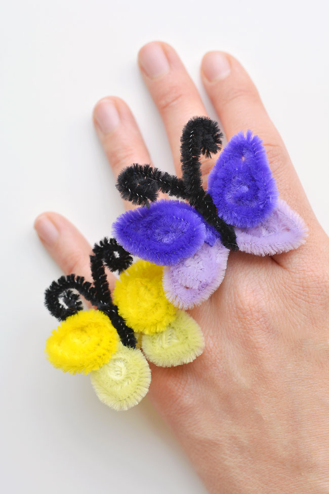 These pipe cleaner butterfly rings are SO SIMPLE to make and they're so pretty! This is such a fun and easy kids craft idea and a super fun summer craft. All you need are a few pipe cleaners and in less than 5 minutes you can make an awesome homemade ring! Wouldn't they be cute to sell at a craft fair?!