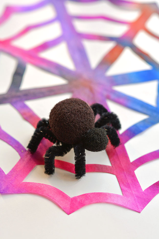 These coffee filter spider webs are SO EASY to make and they look AWESOME! The pipe cleaner and pom pom spider is so simple, but it really makes this Halloween decoration look amazing! This is such a fun Halloween craft for kids and a simple way to make some spooky Halloween decor!