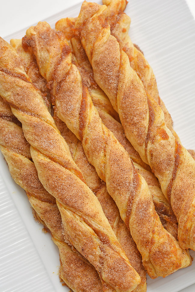 These easy pumpkin pie twists are SO GOOD and really simple to make. This is such a great fall dessert idea and a delicious treat for Thanksgiving or Halloween! They taste amazing sprinkled with cinnamon sugar, or you can dip them in a generous bowl of whipped cream. In less than 20 minutes you can whip up a batch of pumpkin deliciousness. Such a great pumpkin recipe!