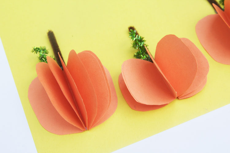For a simple paper craft for fall, make some easy 3D pumpkins. This fall kids craft can be turned into a handmade card or put out for some cute fall decor!