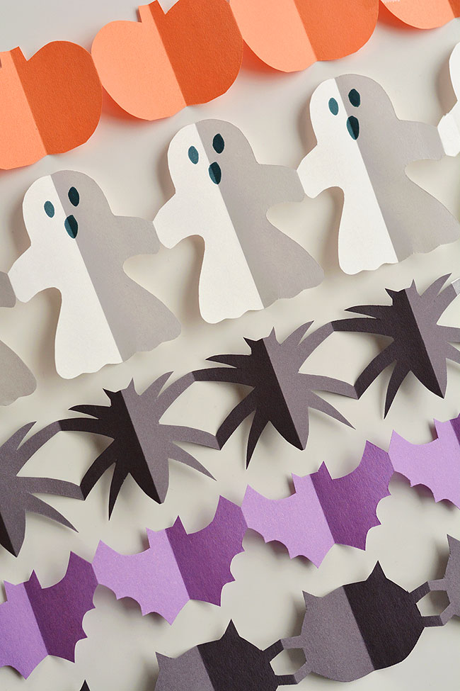 These Halloween paper garland cutouts are SO CUTE and surprisingly simple to make! This is such a fun Halloween craft for kids! Even teens, tweens, adults and seniors would have fun making them! They'd look great hung up on a door, on the walls, or even in the window! What a simple paper craft for kids and a great way to make some non-spooky DIY Halloween decor!